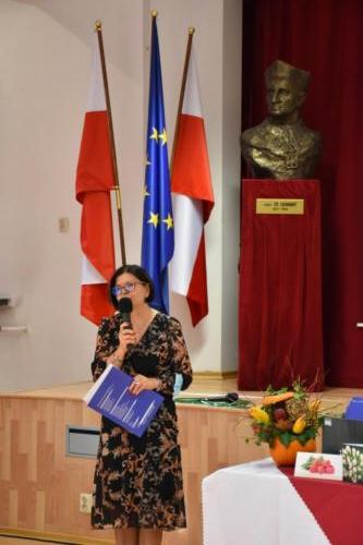 Pani Dyrektor przy mikrofonie, flaga Polski, flaga UE, patron szkoły